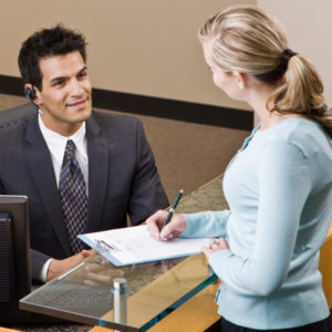 Receptionist man speaking with woman